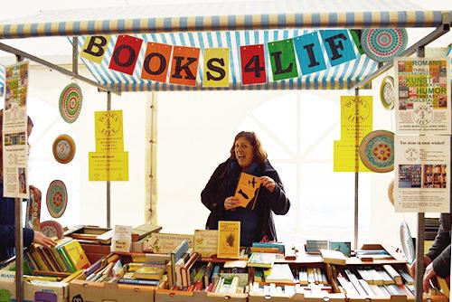 Foto van een vrijwilliger die boeken verkoopt namens Books 4 Life