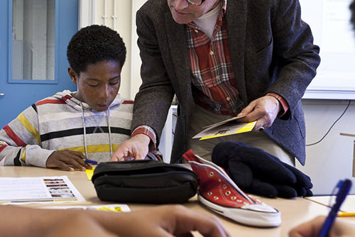 Foto van een docent die iets aanwijst aan een leerling