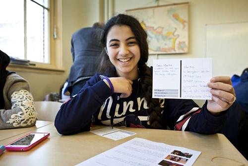 Foto van een meisje dat een beschreven ansichtkaart omhoog houdt