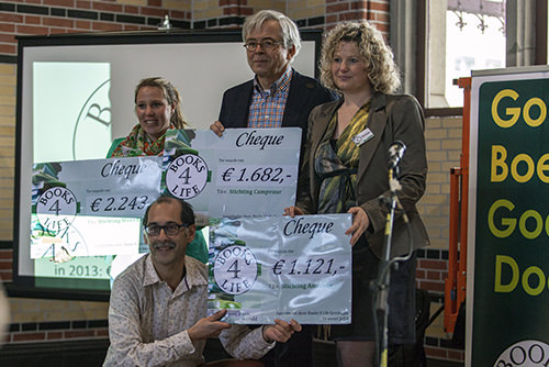 Foto van vier mensen met cheques in hun handen